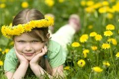 Petite fille de sourire en pissenlits Photo stock