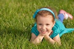 Petite fille de sourire gaie sur l'herbe verte photographie stock libre de droits