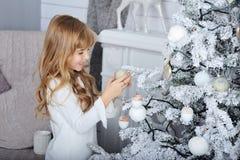Petite fille de sourire heureuse avec la boule de neige près de l'arbre de Noël Photos stock
