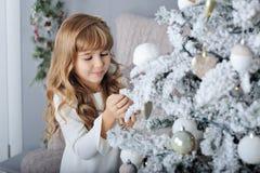 Petite fille de sourire heureuse avec la boule de Noël Image stock