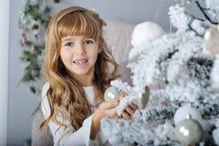 Petite fille de sourire heureuse avec la boule de Noël Image libre de droits