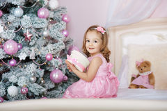 Petite fille de sourire heureuse avec le boîte-cadeau de Noël Photos libres de droits