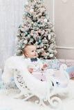 Petite fille de sourire heureuse avec le boîte-cadeau de Noël Photographie stock libre de droits
