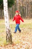 Petite fille de sourire heureuse courant dans la forêt Photo libre de droits