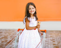 Petite fille de sourire heureuse dans le caddie avec la crème glacée savoureuse Photos libres de droits