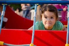 Petite fille de sourire heureuse sur le terrain de jeu Photographie stock libre de droits
