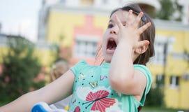 Petite fille de sourire heureuse sur le terrain de jeu Image stock
