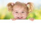 Petite fille de sourire jetant un coup d'oeil derrière un conseil Photographie stock