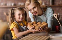 Petite fille de sourire jugeant le plat plein des petits pains Image libre de droits