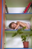 Petite fille de sourire lisant un livre dans une bibliothèque Photographie stock libre de droits