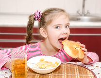 Petite fille de sourire mignonne ayant des céréales de petit déjeuner avec du lait photos stock