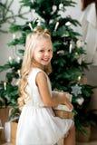 Petite fille de sourire mignonne heureuse avec le boîte-cadeau de Noël Joyeux Noël et bonnes fêtes Photographie stock libre de droits