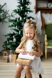 Petite fille de sourire mignonne heureuse avec le boîte-cadeau de Noël Joyeux Noël et bonnes fêtes Images stock