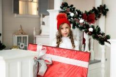 Petite fille de sourire mignonne heureuse avec le boîte-cadeau de Noël Joyeux Noël et bonnes fêtes Image stock