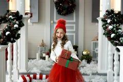 Petite fille de sourire mignonne heureuse avec le boîte-cadeau de Noël Joyeux Noël et bonnes fêtes Photo libre de droits