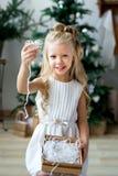 Petite fille de sourire mignonne heureuse avec le boîte-cadeau de Noël Joyeux Noël et bonnes fêtes Photos libres de droits