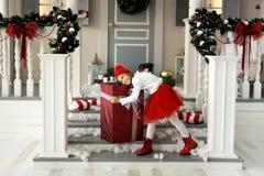 Petite fille de sourire mignonne heureuse avec le boîte-cadeau de Noël Joyeux Noël et bonnes fêtes Photos stock