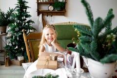 Petite fille de sourire mignonne heureuse avec le boîte-cadeau de Noël Joyeux Noël et bonnes fêtes Images libres de droits