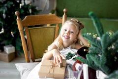 Petite fille de sourire mignonne heureuse avec le boîte-cadeau de Noël Joyeux Noël et bonnes fêtes Photographie stock