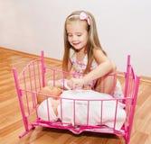 Petite fille de sourire mignonne jouant avec ses poupées nouveau-nées de bébé image stock