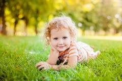 Petite fille de sourire mignonne s'étendant sur l'herbe Photo stock