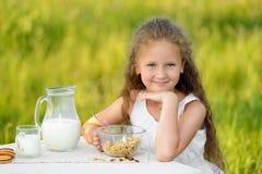 Petite fille de sourire prenant le petit déjeuner extérieur photographie stock