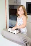 Petite fille de sourire repassant dans la cuisine Photographie stock