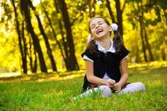 Petite fille de sourire s'asseyant sur l'herbe image stock