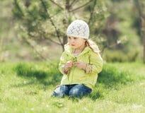 Petite fille de sourire s'asseyant sur une pelouse en parc Photo libre de droits