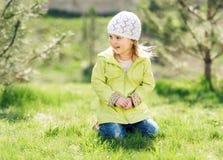 Petite fille de sourire s'asseyant sur une pelouse en parc Photos libres de droits