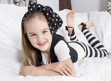 Petite fille de sourire se trouvant sur le divan Photographie stock