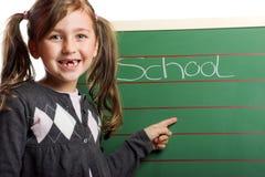 Petite fille de sourire sur un panneau Image stock