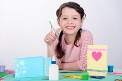 Petite fille de sourire tenant des ciseaux photos libres de droits