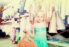 Petite fille de sourire tenant des paniers dans la boutique Photo libre de droits