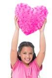 Petite fille de sourire tenant le coussin sous forme de coeur Photo libre de droits