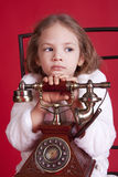 Petite fille de Thougtful avec le vieux téléphone Photo stock