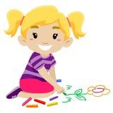 Petite fille dessinant une fleur utilisant la craie Images stock