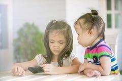 Petite fille deux asiatique s'asseyant sur la chaise utilisant le téléphone portable Photos stock
