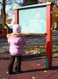 Petite fille devant la table d'école Images stock