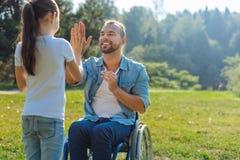 Petite fille donnant à son père handicapé de hauts cinq Photos libres de droits