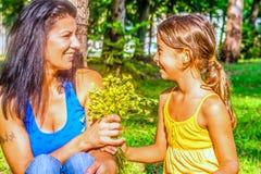 Petite fille donnant des fleurs de maman image stock