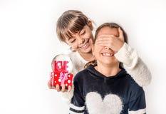 Petite fille donnant le cadeau d'amour de surprise à son ami avec b blanc Photos stock