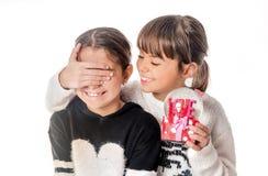 Petite fille donnant le cadeau d'amour de surprise à son ami avec b blanc Photo libre de droits