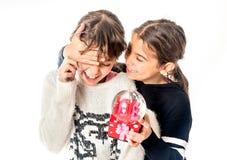Petite fille donnant le cadeau d'amour de surprise à son ami avec b blanc Photo stock