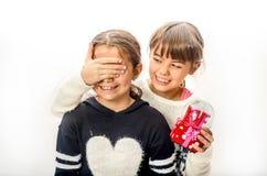 Petite fille donnant le cadeau d'amour de surprise à son ami avec b blanc Image stock