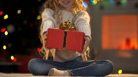 Petite fille donnant Noël actuel à la caméra, charité sur la bienveillance de Noël photo stock