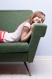 Petite fille dormant doucement sur un sofa vert Photo stock
