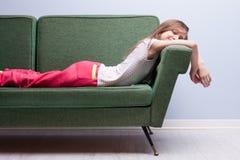 Petite fille dormant doucement sur un sofa vert Image stock