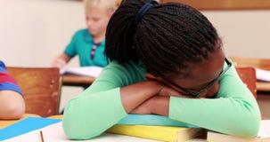 Petite fille dormant sur un livre dans la salle de classe clips vidéos