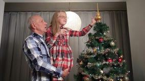 Petite fille douce ajustant le dessus d'arbre de Noël banque de vidéos